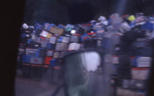 image from moving car of piles of car batteries